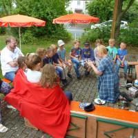 Vorführung von Steinzeitfeuerzeugen durch Claudia Jüngling vor Euerbacher Kindern und Vorsitzendem Jochen Kraft